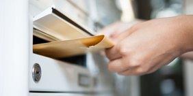 Hand wirft Brief in den Briefkasten