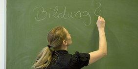 Eine Schülerin schreibt das Wort Bildung an die Tafel.