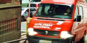 """Der rote Bus der DGB-Jugend Berufsschultour mit weißer Aufschrift """"Gemeinsam gewinnen"""" passiert gerade die Schranke eines Parkplatzes"""