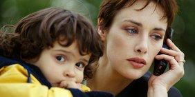 Frau mit Kind und Handy im Arm