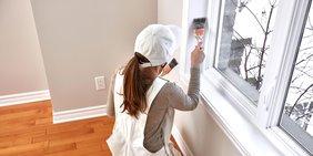 junge Malerin streicht mit dem Pinsel in einer Wohnung um ein Fenster herum