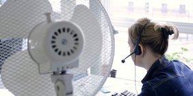 Frau mt Headset in einem Call Canter / Callcenter / Büro, im Vordergrund ein Ventilator (Sommer/Hitze)