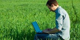 Mann mit Laptop auf einer Wiese