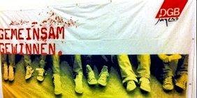 """DGB-Jugend-Transparent Gemeinsam Gewinnen: Man sieht nur die Unterschenkel von Jugendlichen in Jeans und Turnschuhen, die unter einem weißen Transparent mit der DGB-Jugend-Raute und der Aufschrift """"Gemeinsam gewinnen"""" auf dem Boden hocken."""