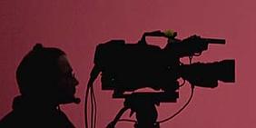 Fernsehkamera vor reotem Hintergrund