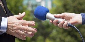 Interview mit zwei Personen mit blauen Mikrofon